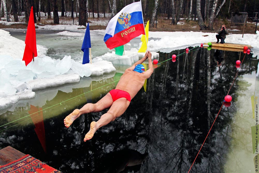Member of a local swimming club holds a Russian national flag as he dives in at the start of a 24-hour swimming marathon near the western Siberian city of Barnaul