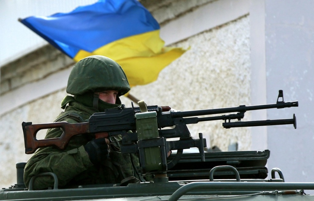 An armed man, believed to be Russian serviceman, stands guard outside an Ukrainian military base in Perevalnoye