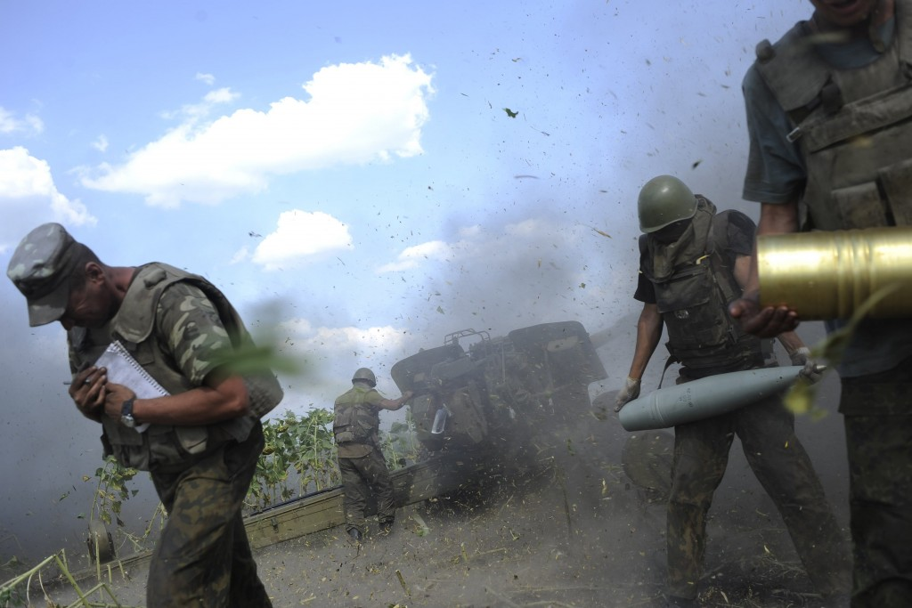 Ukrainian servicemen, who are members of an artillery section, take cover after firing a cannon during a military operation against pro-Russian separatists near Pervomaisk, Luhansk region August 2, 2014. REUTERS/Maks Levin (UKRAINE - Tags: MILITARY POLITICS CIVIL UNREST CONFLICT TPX IMAGES OF THE DAY)