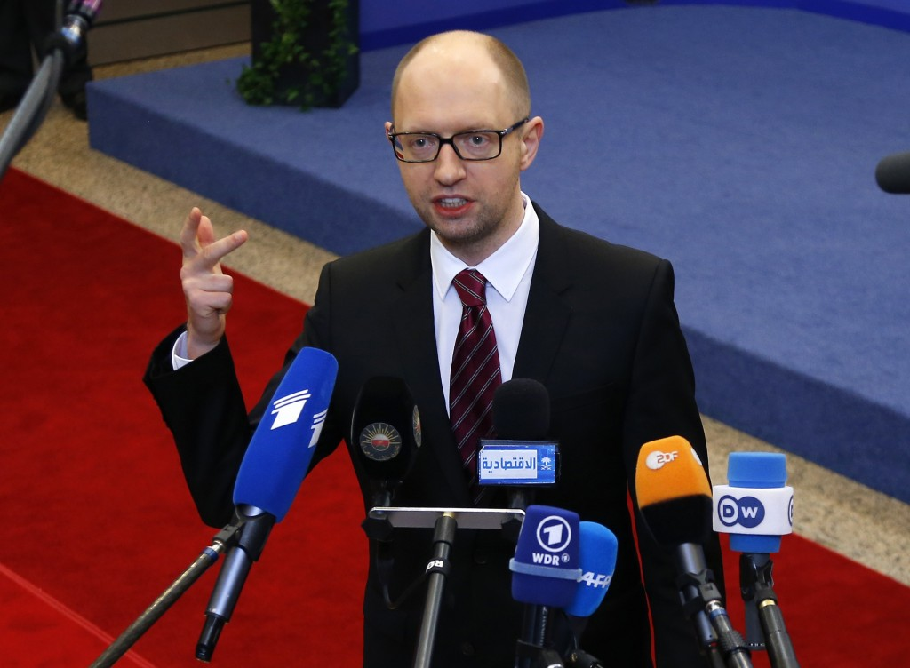Ukraine's Prime Minister Arseniy Yatsenyuk talks to reporters while leaving a European Union leaders summit in Brussels March 21, 2014. The European Union and Ukraine's interim government signed a political association agreement on Friday, committing to the same deal former president Viktor Yanukovich rejected last November, a move that lead to his overthrow.    REUTERS/Yves Herman (BELGIUM - Tags: POLITICS)